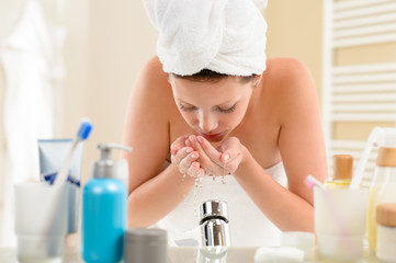 Woman washing face above bathroom sink