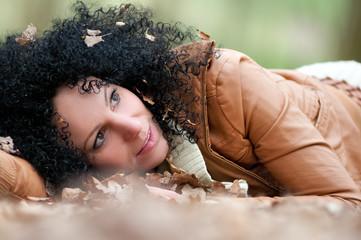 junge Frau liegt im Herbstlaub
