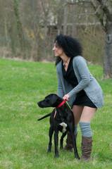 junge frau mit locken hält ihren hund fest