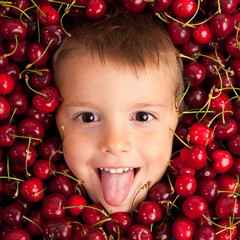 Kid smiling face portrait surrounded by cherries.