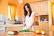 Young woman cutting vegetables smiles in kitchen
