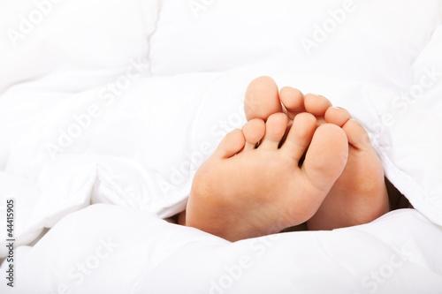 Weibliche kleine Füße unter der Bettdecke