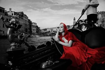 Beautifiul woman in red cloak riding on gandola