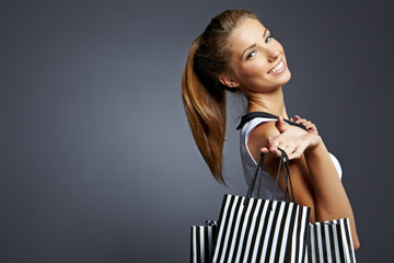 Shopping woman holding bags,  isolated on gray studio background