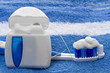 dental floss and toothbrush on a towel