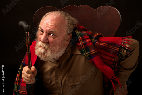 Old man scowls, leans forward and shakes his cane