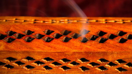 Incense stick in a wooden holder with red silk background, artit