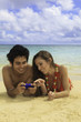 couple with their cell phone, texting on the beach