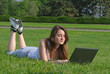 Girl lying on grass with her laptop