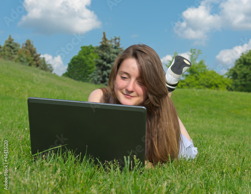 Smiling woman using a laptop outdoors