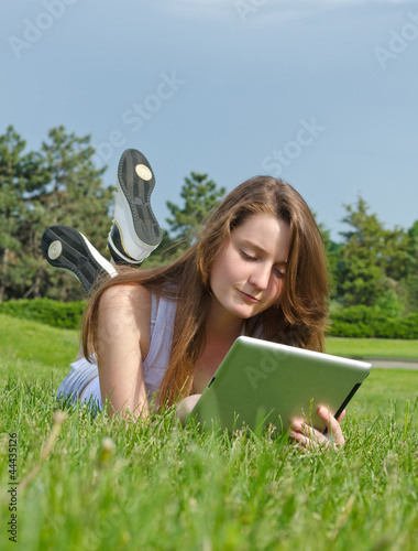 Young girl using a tablet in the park