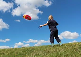 Kind spielt mit Lenkdrachen