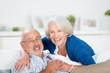 glückliches älteres paar umarmt sich auf dem sofa