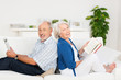 lachendes senioren-paar mit buch und tablet