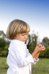 Crying young boy with finger injury outdoors