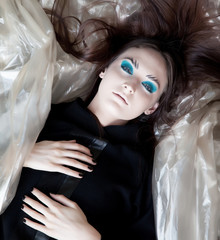 Beauty bright woman lying on a pieces of fashion fabrics