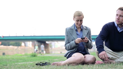 Young business people with cellphone relaxing outdoors