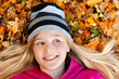girl on autumn leaves smiling and looking sideways