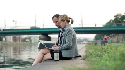 Business people with laptop having a break in city