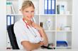Junge Ärztin sitzt am Schreibtisch
