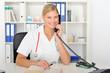 Junge Ärztin telefoniert in der Praxis