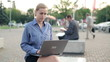 Portrait of happy businesswoman with laptop in the city