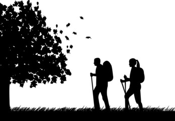 Hiking couple with rucksacks in autumn or fall silhouette