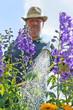 Mann gießt Blumen im Garten