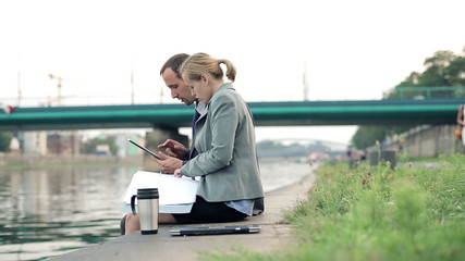 Happy business couple with documents and tablet computer
