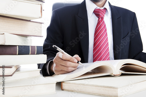 Businessman writes on a book