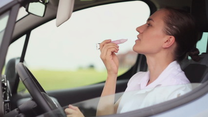 Young woman with lipstick in the car