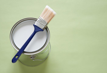 Paintbrush and a can of white paint on green background