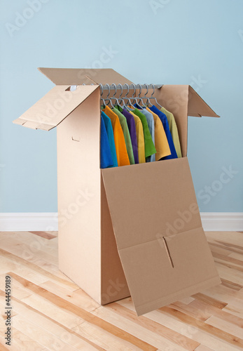 Wardrobe box with colorful clothing, ready for moving