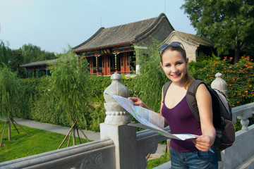 Caucasian woman with map and backpack travel in China