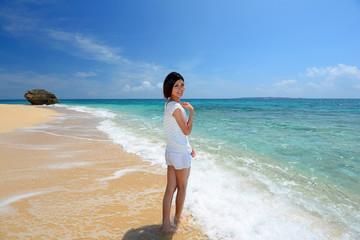 波打ち際を散歩する笑顔の女性