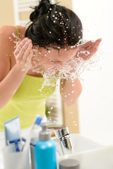 Woman splashing water on face in bathroom