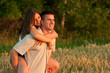 Young couple piggyback riding while watching sunset