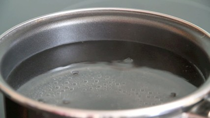 Steam of boiling water on stove in kitchen