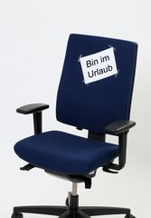 """Buerostuhl mit Zettel worauf steht:""""Bin in Urlaub"""""""