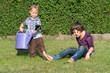 Kinder spielen mit Gießkanne im Grünen