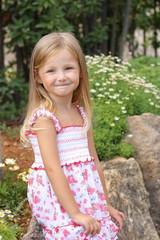 Little girl in garden on a background of flowers
