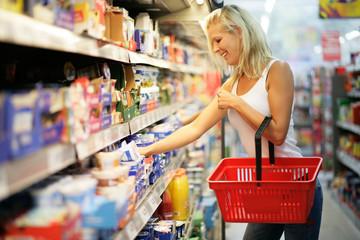 Frau mit rotem Einkaufskorb im Supermarkt