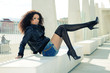 Funny black female model at fashion with high heels sitting on a
