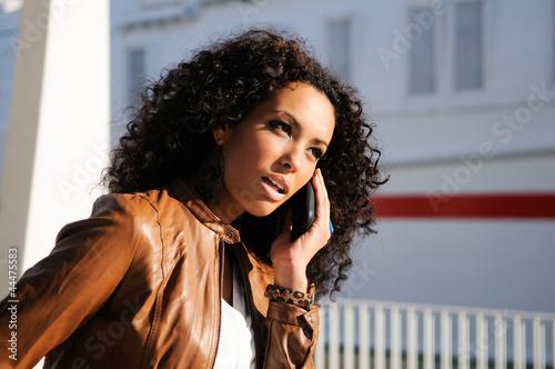 Portrait of pretty blak woman in urban background talking on pho