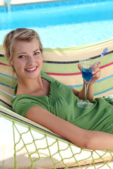 a woman drinking a cocktail near a swimming-pool