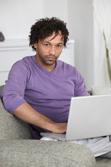 unhappy man doing computer on a couch