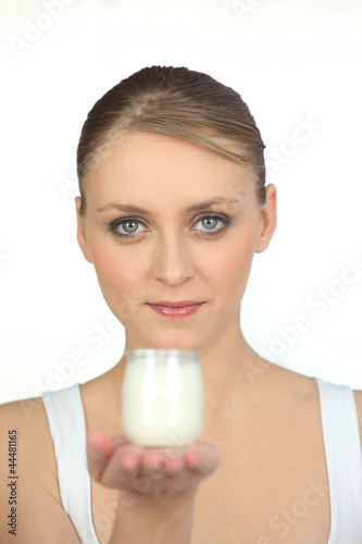 Young woman with yoghurt on a white background
