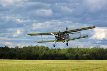 Historic airborne biplane landing at airfield.