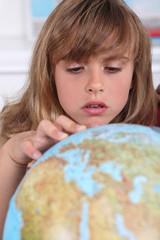 Young girl examining a globe