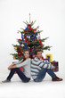 Couple sitting in front of their Christmas tree